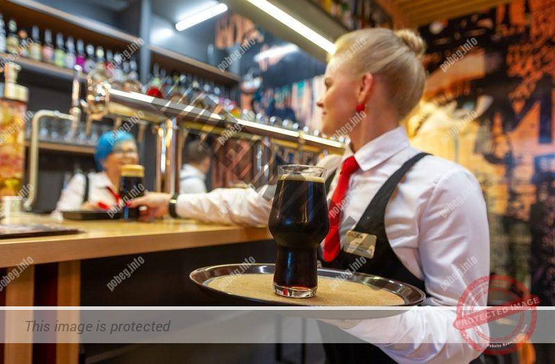Русская девушка, официантка в баре с бокалом пива