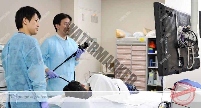Два врачаь осматривают пациента в японской больнице