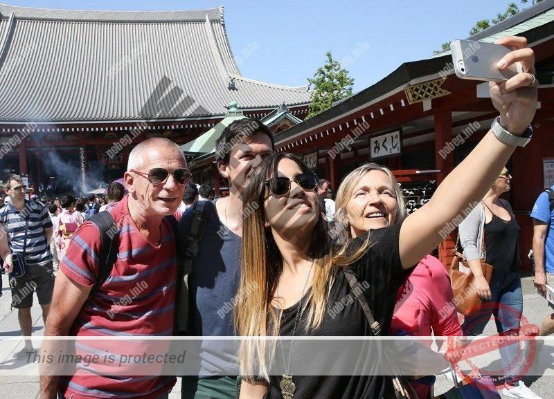 Туристы из Европы фотографируются в японском храме
