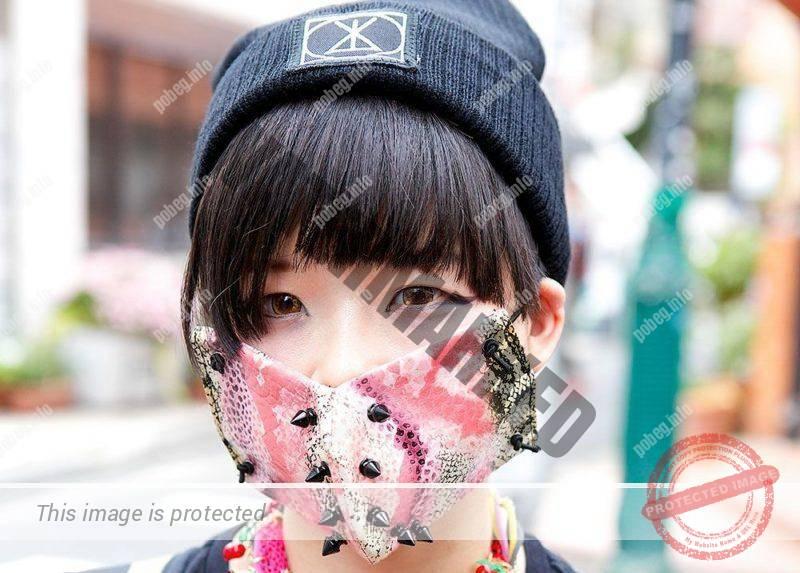 Японская девушка в розовой маске на лице