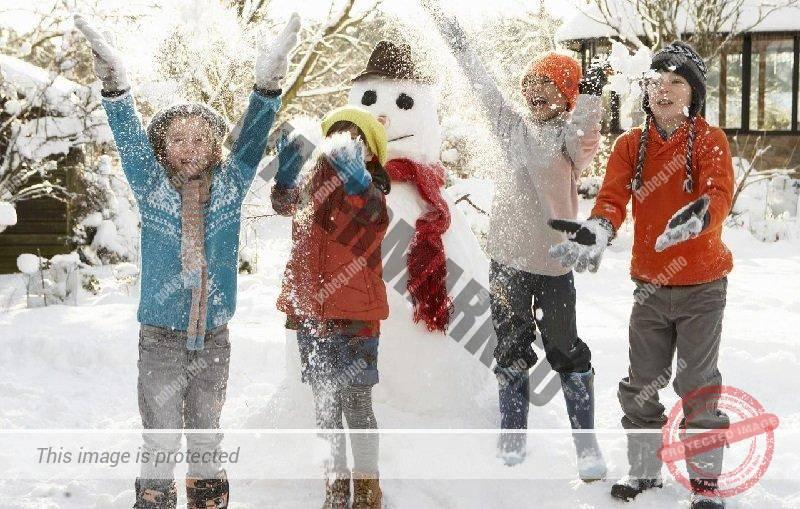 Немецкие дети играют на улице зимой на фоне снеговика