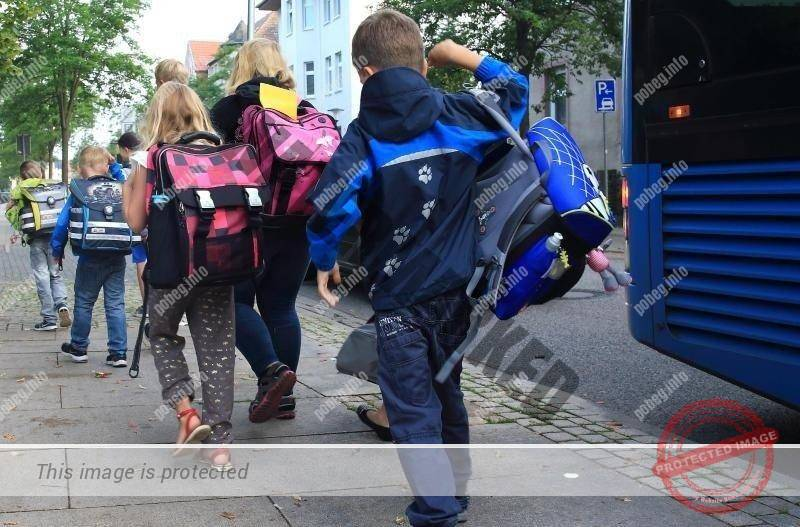 Немецкие дети идут в школу после автобуса, младшие классы